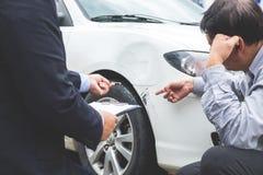 Équipez l'agent voiture près endommagée et de examen de Filling Insurance Form, Images libres de droits