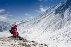 Équipez l'alpiniste assis sur la montagne couverte par neige dans le jour d'hiver ensoleillé Photos stock