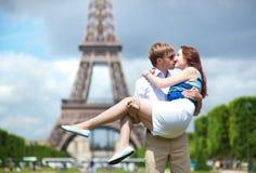 Équipez l'amie de transport dans des ses bras à Paris Photo stock