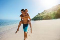 Équipez l'amie de transport sur le sien de retour le long de la plage Photographie stock libre de droits