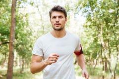 Équipez l'athlète avec le handband fonctionnant dehors pendant le matin photographie stock