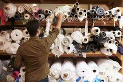 Équipez l'atteinte pour sélectionner le tissu des étagères de stockage Image stock