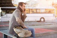 Équipez l'attente à la gare routière et parler au téléphone portable images libres de droits