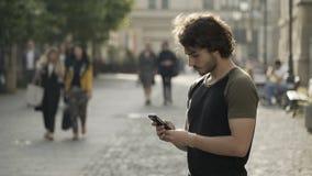 Équipez l'attente dans un endroit urbain public des amis textotant sur le media social APP sur son smartphone clips vidéos