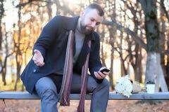 Équipez l'attente sur un banc la date en parc d'automne Images libres de droits