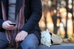 Équipez l'attente sur un banc la date en parc d'automne Photo stock