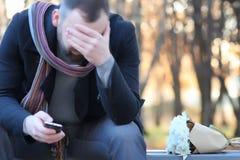 Équipez l'attente sur un banc la date en parc d'automne Image libre de droits