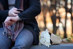 Équipez l'attente sur un banc la date en parc d'automne Photo libre de droits