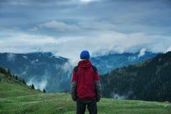 Équipez l'aventurier observant le mouvement des nuages lourds Images stock