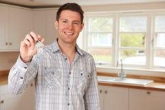 Équipez l'entrée dans la nouvelle maison tenant des clés sur le porte-clés formé par Chambre Photo stock