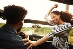Équipez l'entraînement avec la passagère enthousiaste de femme devant la voiture Photos libres de droits