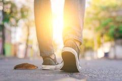 Équipez l'espadrille et les jeans de port marchant le long de la rue de ville Photographie stock libre de droits