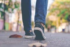 Équipez l'espadrille et les jeans de port marchant le long de la rue de ville Image libre de droits