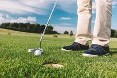Équipez l'essai de mettre une balle de golf dans le trou Photos libres de droits