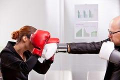 Équipez l'essai de poinçonner une femme dans un match de boîte Photographie stock libre de droits