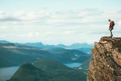 Équipez l'explorateur se tenant sur le seul sommet de montagne de falaise image stock