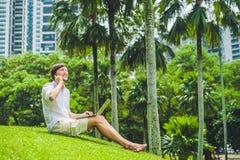 Équipez l'homme d'affaires ou l'étudiant dans le tenue décontractée utilisant l'ordinateur portable en parc tropical sur le fond  photo libre de droits