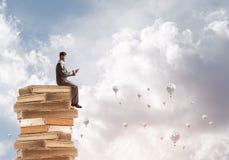 Équipez l'homme d'affaires sur le livre de lecture de pile et les aérostats volant autour Photo libre de droits