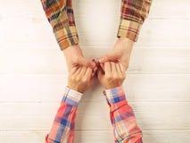 Équipez l'image de vue supérieure de main du ` s de femme de prise sur le fond en bois Photo libre de droits