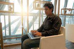 Équipez l'ordinateur portable d'utilisation dans le salon d'aéroport dans le temps de matin Photos stock