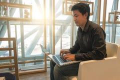 Équipez l'ordinateur portable d'utilisation dans le salon d'aéroport dans le temps de matin Images libres de droits