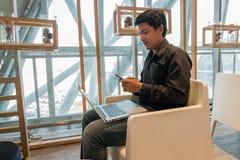 Équipez l'ordinateur portable d'utilisation et le téléphone intelligent dans le salon d'aéroport Photographie stock