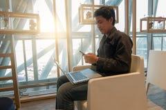 Équipez l'ordinateur portable d'utilisation et le téléphone intelligent dans le salon d'aéroport dans le temps de matin Photographie stock libre de droits