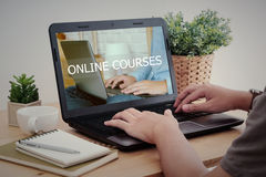 Équipez l'ordinateur portable de dactylographie de main avec des cours en ligne sur l'écran Photographie stock libre de droits