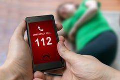 Équipez l'urgence de composition (nombre 112) sur le smartphone La femme a eu pour entendre Photographie stock
