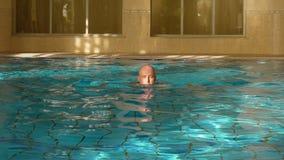 Équipez la brasse de natation dans la piscine d'intérieur, vue de face Style de vie folâtre banque de vidéos