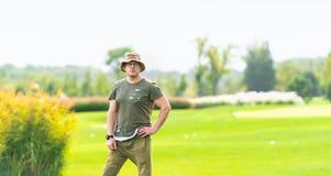 Équipez la chemise verte de port se tenant dans le domaine herbeux photo stock
