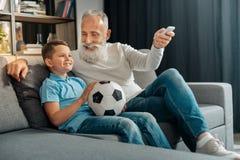 Équipez la climatisation de rotation dessus tout en observant le football avec le petit-fils Images libres de droits