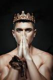 Équipez la couronne sur sa tête pour prier avec les mains pliées images stock