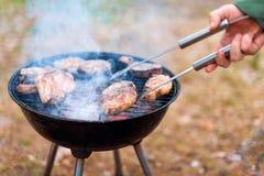 Équipez la cuisson, seulement les mains, il grille la viande ou le bifteck pour un plat Viande grillée délicieuse sur le gril Wee images libres de droits