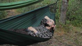 Équipez la détente dans l'hamac chez l'homme de forêt de vert d'été avec la barbe et les verres banque de vidéos