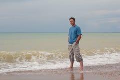 Équipez la détente sur la plage et la vague approchante photo stock