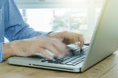 Équipez la dactylographie sur l'ordinateur portable d'ordinateur dans le mouvement brouillé Images stock