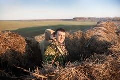 Équipez la dissimulation dans la meule de foin pendant la saison de chasse au lever de soleil Photographie stock