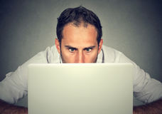 Équipez la dissimulation derrière un ordinateur portable regardant fixement l'écran avec une expression choquée de visage photo libre de droits