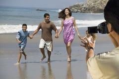 Équipez la famille latine hispanique heureuse d'enregistrement vidéo marchant à la plage image libre de droits