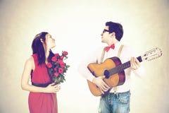 Équipez la femme de approche jouant une chanson d'amour, sérénade Photo stock