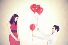 Équipez la femme de approche lui donnant les ballons rouges de forme de coeur dans un jour du ` s de valentine Image stock