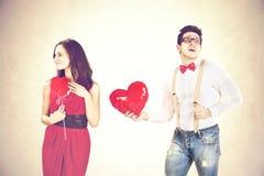 Équipez la femme de approche lui donnant les ballons rouges de forme de coeur dans un jour du ` s de valentine Photo libre de droits