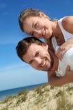 Équipez la femme de transport sur son dos sur la plage Image stock