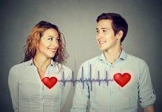 Équipez la femme regardant l'un l'autre avec les coeurs rouges liés par le cardiogramme Images libres de droits