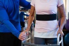 Équipez la femme supérieure de aide pour marcher avec le marcheur Photos stock