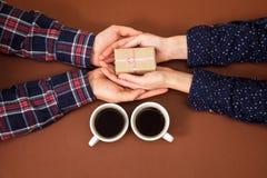 Équipez la femme tenant la boîte d'histoire d'amour de vintage de fond de brun de Saint Valentin de cadeau de mains de café de ta Images libres de droits