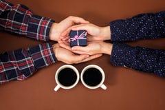 Équipez la femme tenant la boîte d'histoire d'amour de vintage de fond de brun de Saint Valentin de cadeau de mains de café de ta Photos stock