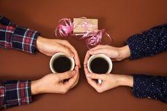 Équipez la femme tenant la boîte d'histoire d'amour de vintage de fond de brun de Saint Valentin de cadeau de mains de café de ta Photos libres de droits