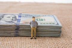 Équipez la figurine près du paquet du billet de banque de dollar US Photo libre de droits
